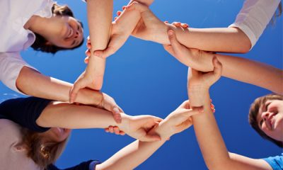 group of people holding hands each other